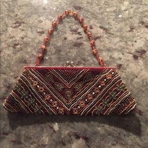 Maroon color beaded hand bag.